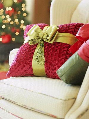 Red & green pillows on a beige chair