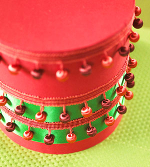 Red cylinder with pom poms and green ribbon