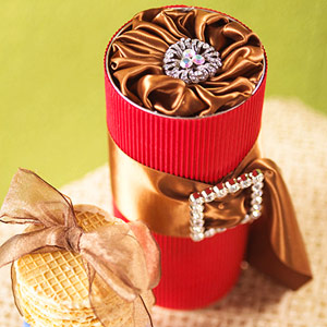 red cylinder with brown lid and brown ribbon with buckle