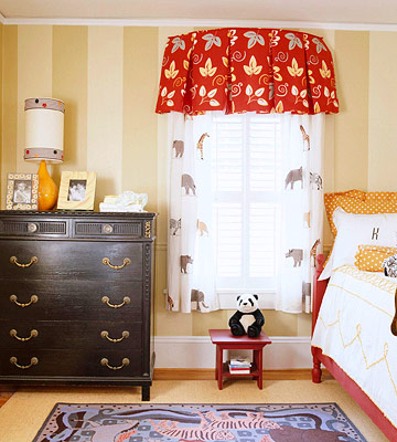 bedroom with tan striped walls and red valance