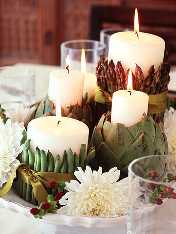 Thanksgiving table centerpiece with mums and candles wrapped in green beans and artichokes