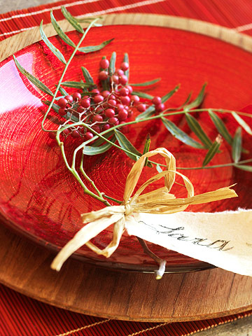 A Thanksgiving table decoration complete with red berries with green leafy stems, a tan raffi bow and name card placed within a round red bowl