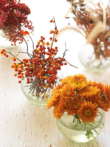 Thanksgiving table decorations with vases filled with autumn flowers and berries