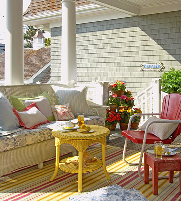 porch with wicker furniture and yellow table