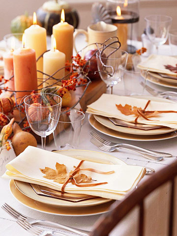 Thanksgiving table decorated with leaves, gourds, branches and candles