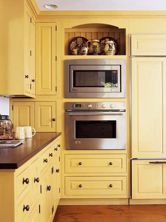 yellow cabinets with built-in oven and microwave