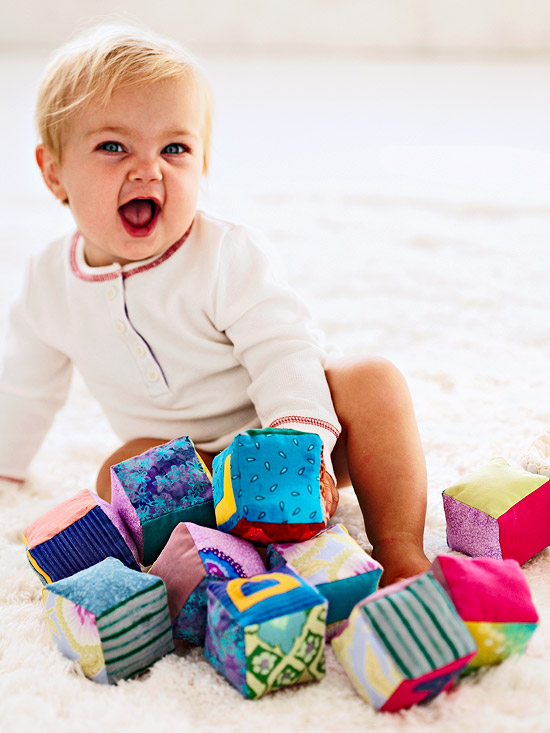 blonde baby on white carpet with colorful blocks