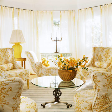 white and yellow chairs around a round glass coffee table