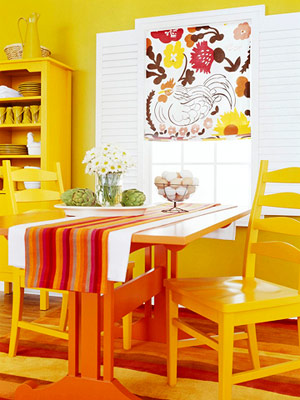 yellow dining room with orange table and retro curtain