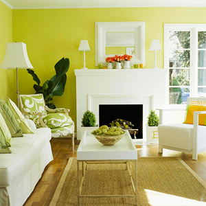 green living room with white fireplace and wood trim