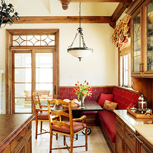 red banquette in a white kitchen with wood trim and beams
