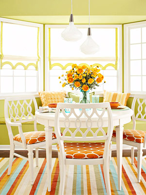 green walls with white dining set, orange, and blue linens