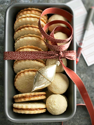 Alfajores and Butter Mint Cookies in loaf pan with crimson ribbon and ornament