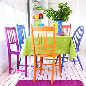 white washed dining room with orange, blue, green, and purple painted chairs