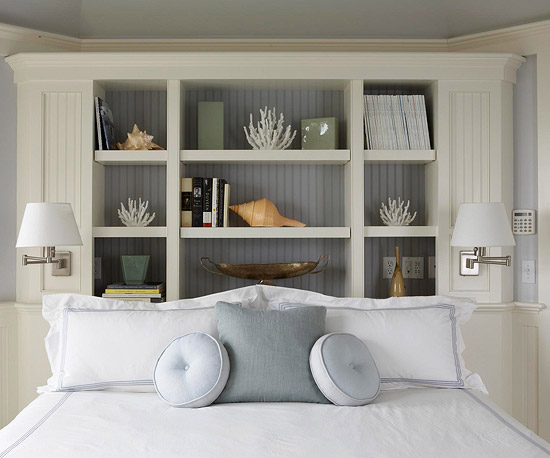 bedroom with storage headboard and white wainscoting