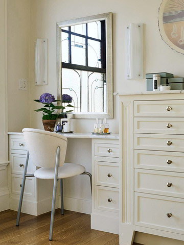 white built-in vanity table with storage drawers and wall sconces