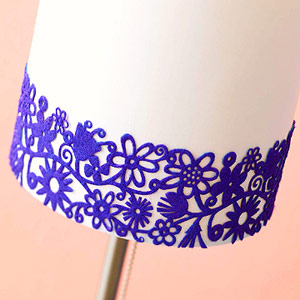 Close-up of laser-cut felt ribbon wrapped around bottom of white lampshade