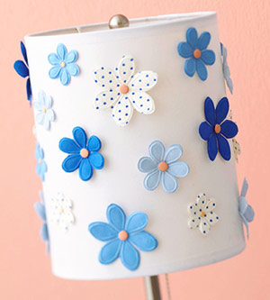 Close-up of lampshade covered in scrapbooking flower accents, adhered with pink brads and hot glue