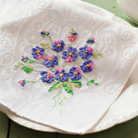 White napkin with a ribbon embroidered pansy