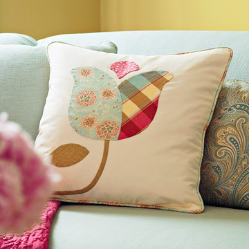Applique tulip pillow propped up against paisley pillow on a mint green couch