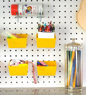 Yellow boxes hang from a pegboard; glass cylinder container holds pencils.