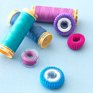 Bobbins with ponytail holders to keep thread in place