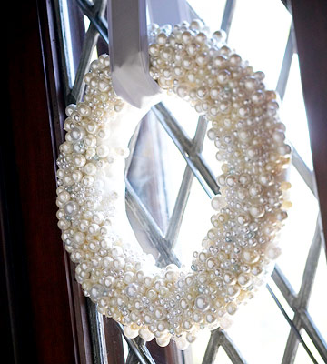White pearl wreath hanging by ribbon from doorway