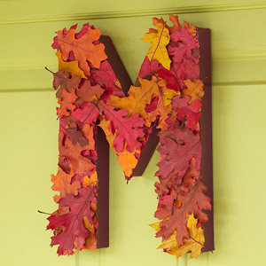 Letter covered in fall leaves on green front door