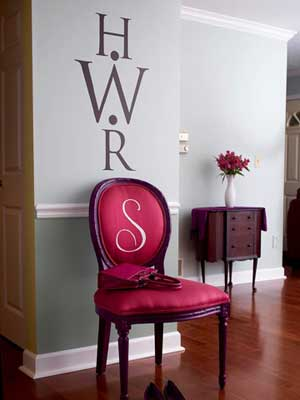 Wall with monogram on it and monogrammed chair below