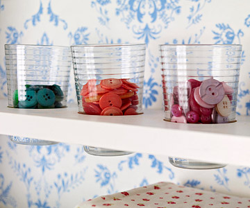 Glasses with colored buttons tucked into storage shelf