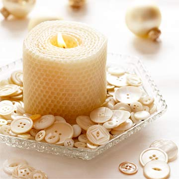 White beeswax candle in a dish surrounded by buttons