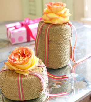 Peach roses as bows on woven gift boxes