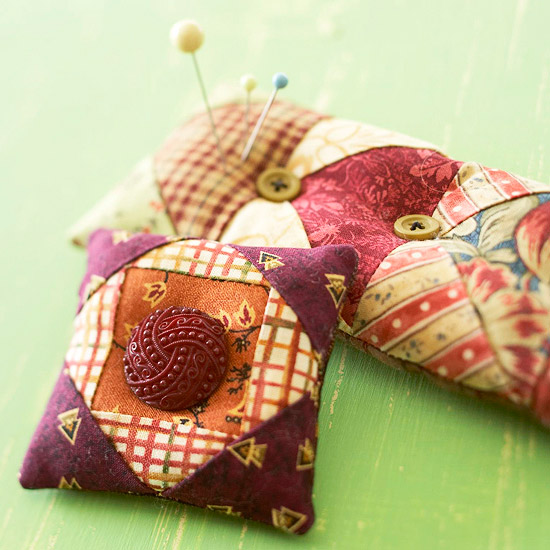 Two quilt pattern pincushions made from fabric scraps