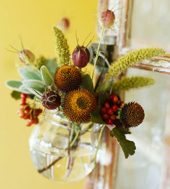Glass vase filled with herbs, pods, flowers, and berries