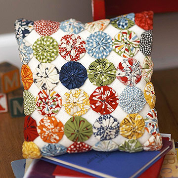 White pillow with colorful fabric yo-yos on stack of books