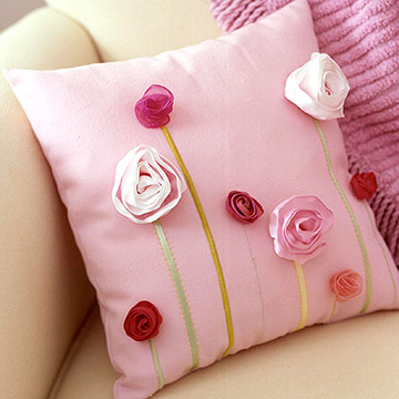 Pink pillow with pink ribbon blooms and green ribbon stems