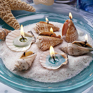 Seashell candles in dish with sand