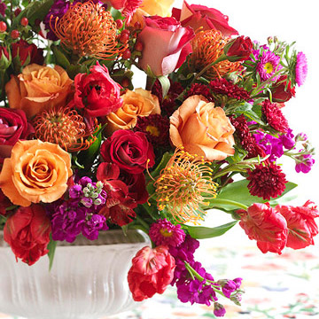Bright warm colored flowers in white traditional vase