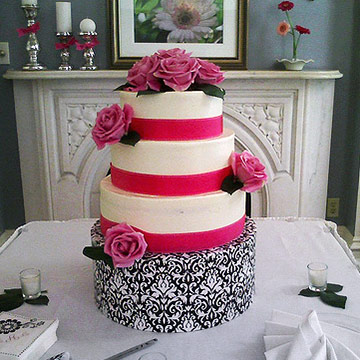 Primarily white cake with pink ribbon and damask patterned stand