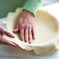 Pressing piecrust dough into pie plate