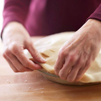 Folding the top pastry edge under the bottom pastry edge