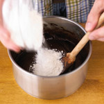 Adding flour to brownies