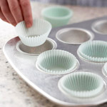 Lining muffin pan with paper liners