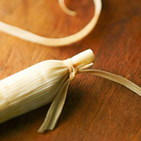 Tying one end of a tamale
