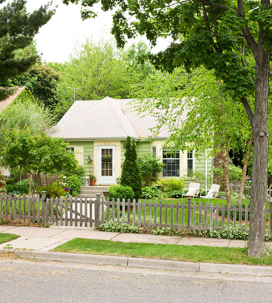 Front of home with picket fence and greenery