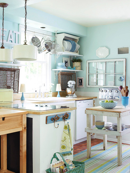 Blue kitchen with hanging pots and pans above sink.
