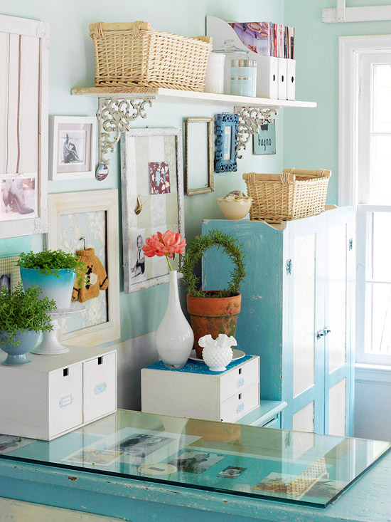 Famed photos on wall with blue cabinet and desk