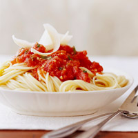 Marinara Sauce with spaghetti in large white bowl with large fork and spoon