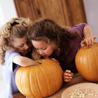 2 girls removing pumpkin seeds