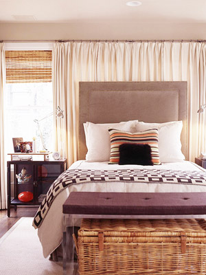 Tall brown headboard against curtained wall